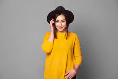 Portrait of fashion teen girl over grey background. Beautiful trendy woman in yellow sweater and hat royalty free stock images
