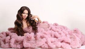 Portrait of fashion woman in gorgeous long pink dress with makeu. P and long wavy healthy hair style, pendant jewelry, brunette isolated on white studio Royalty Free Stock Image