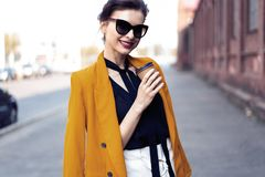 Portrait fashion woman in sunglasses walking on street . She wears yellow jacket, smiling to side. royalty free stock photography