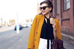 Portrait fashion woman in sunglasses walking on street . She wears yellow jacket, smiling to side. stock photo