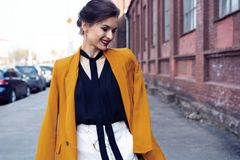 Portrait fashion woman walking on street . She wears yellow jacket, smiling to side. royalty free stock images