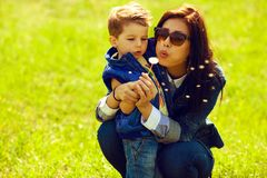 Portrait of fashionable baby boy and mum with dandelion. Portrait of fashionable baby boy and his gorgeous mother in trendy sunglasses playing with dandelion in Stock Image
