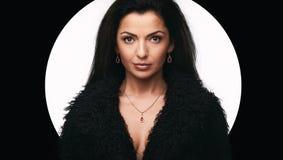 Fashionable beautiful woman wearing jewelry. Portrait of fashionable beautiful woman in black fur coat wearing jewelry stock images