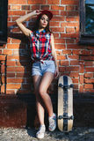 Portrait of fashionable beautiful young woman with a skateboard Royalty Free Stock Photos