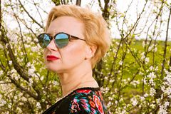 Portrait of fashionable blonde woman posing wearing shades. Outside on countryside background with copypsace advertising area Stock Photo