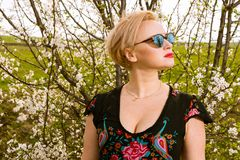 Portrait of fashionable blonde woman posing wearing shades. Outside on countryside background with copypsace advertising area Royalty Free Stock Image