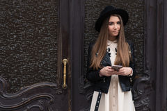 Portrait of a fashionable brunette woman with cool look holding mobile phone while standing on the street against wooden door Royalty Free Stock Photos