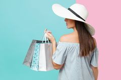 Portrait fashionable elegant fashion beautiful caucasian woman in summer dress, white large wide brim sun hat holding. Packages bags with purchases after royalty free stock image