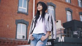 Portrait of a fashionable girl on the background of the architecture of the city. beautiful young woman in jeans and. Jacket stock video footage