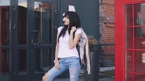 Portrait of a fashionable girl on the background of the architecture of the city. beautiful young woman in jeans and stock footage