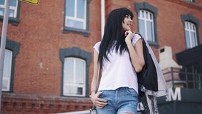 Portrait of a fashionable girl on the background of the architecture of the city. beautiful young woman in jeans and stock video footage