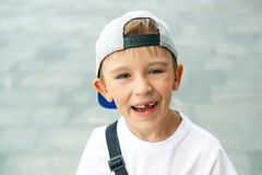 Portrait of fashionable little boy in baseball cap. Happy childhood. Cute little boy without teeth smiles outdoors