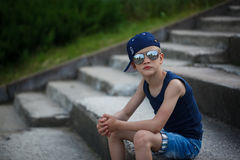 Portrait of Fashionable little boy in sunglasses and cap. Childh Royalty Free Stock Images