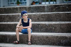 Portrait of Fashionable little boy in sunglasses and cap siting Stock Photos