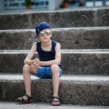 Portrait of Fashionable little boy in sunglasses and cap siting Royalty Free Stock Photography