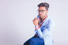 Portrait of fashionable man wearing glasses. Portrait of fashionable man, seated, wearing glasses while thinking and looking away in studio background Royalty Free Stock Image
