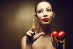 Portrait of a fashionable model holding red heart Royalty Free Stock Photography