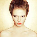 Portrait of fashionable model with retro hairdo, arty make-up. Portrait of a fashionable model with retro hairdo and arty make-up of golden foil posing over royalty free stock images