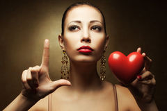 Portrait of fashionable model with sexy red lips holding red heart Royalty Free Stock Photography
