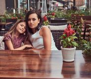 Portrait of fashionable mom and her lovely daughter during a time in an outdoor cafe. Happy fashionable family Royalty Free Stock Images