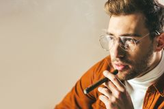 Portrait of fashionable pensive man smoking cigar and looking away. Isolated on beige Stock Images