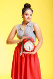 Portrait of fashionable pin-up girl woman holding red clock Stock Images