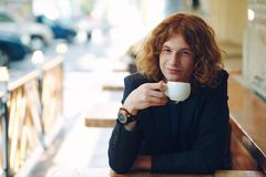 Portrait fashionable reddish man drinking coffee. Portrait smiling fashionable interesting man with curly reddish hair, wearing jacket and vintage watch royalty free stock photos