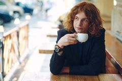 Portrait fashionable reddish man drinking coffee. Portrait young fashionable interesting man with curly reddish hair, wearing jacket and vintage watch, drinking Royalty Free Stock Photography