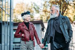 Portrait of fashionable senior couple holding hands and looking at each other. On street royalty free stock photo