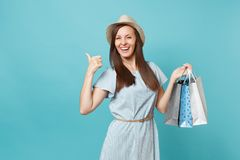 Portrait fashionable smiling beautiful caucasian woman in summer dress, straw hat holding packages bags with purchases stock images
