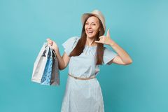 Portrait fashionable smiling beautiful caucasian woman in summer dress, straw hat holding packages bags with purchases royalty free stock image