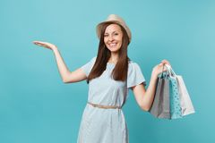 Portrait fashionable smiling beautiful caucasian woman in summer dress, straw hat holding packages bags with purchases stock image