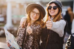 Portrait fashionable smiling girls expressing brightful emotions on sunny day in city. Happy travelling together, lovely royalty free stock photography