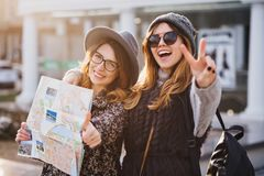Portrait fashionable smiling girls expressing brightful emotions on sunny day in city. Happy travelling together, lovely stock image