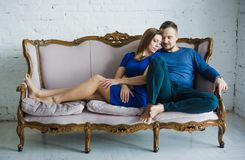 Portrait of a fashionable stylish couple sitting together with bare feet on the couch in the living room, embracing, smiling, stock photo