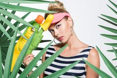 Fashionable woman with water gun Royalty Free Stock Photos