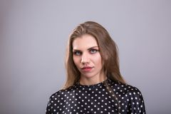 Fashionable woman dressed in a blouse for polka dots, standing on the gray background Royalty Free Stock Photo