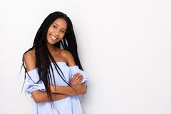 Fashionable young african woman with braided hairstyle standing with arms crosses against white background. Portrait of fashionable young african woman with Royalty Free Stock Photo
