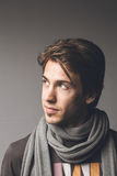 Fashionable man in scarf. Portrait of fashionable young man with gray scarf, studio background Stock Photo