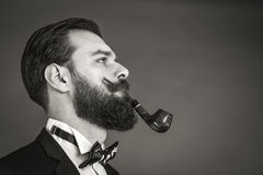 Portrait of a fashionable young man with retro look smoking pipe Royalty Free Stock Photo