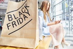 Young Woman Shopping on Black Friday. Portrait of fashionable young woman using smartphone while sitting on bench in shopping mall, BLACK FRIDAY paper back in Royalty Free Stock Photos