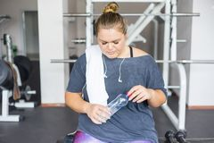 Fat girl in a gym. A portrait of a fat girl exercising in a gym royalty free stock image