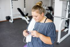 Fat girl in a gym. A portrait of a fat girl exercising in a gym stock image