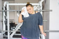 Fat girl in a gym. A portrait of a fat girl exercising in a gym stock images