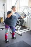 Fat girl in a gym. A portrait of a fat girl exercising in a gym stock photo