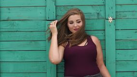 Portrait of a fat girl with long hair in the Park. Plus size model posing on camera in a Park near a green vintage wooden wall. Long hair. Slow motion stock video footage