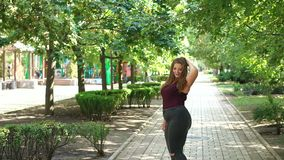 Portrait of a fat girl with long hair in the Park. Uncomplexed young girl overweight posing in the Park in the summer among the green trees. Plus size model stock footage