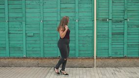 Portrait of a fat girl with long hair in the Park. A young girl with excess weight is dressed in ragged jeans and a tank top, walking in the summer in the park stock video footage