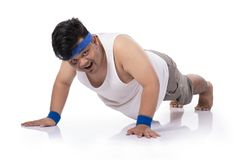 Portrait of fat young man try harder doing push up. Portrait of fat young man happies doing push up and look to camera royalty free stock image