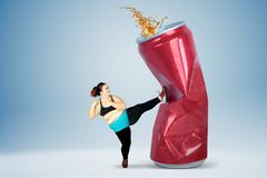Fat woman kicking soft drink stock image